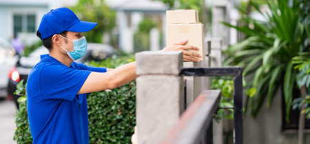 Panoramic side view asian deliver man with face mask in blue shirt handling packages and put in on the fence post as contactless shopping delivery. This can reduce coronavirus COVID-19 spreading.