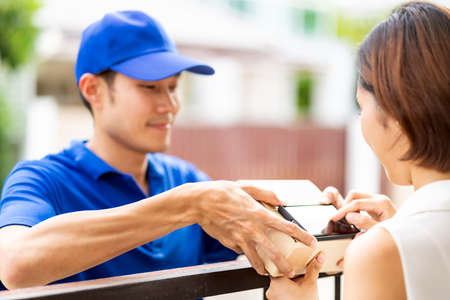 Asian woman sign electronic signature to portable mobile device after receive package from male delivery man in blue shirt. Package shopping delivery and digital sign concept.
