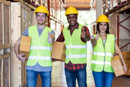 Portrait of caucasian white and african black warehouse workers hold cardboard box packaging in warehouse distribution center environment. Using in business warehouse diversity and logistic concept. Banque d'images