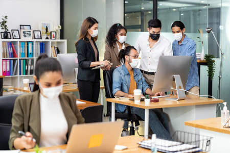 Group portrait of interracial business worker team wear protective face mask in new normal office with social distance practice prevent coronavirus COVID-19 spreading
