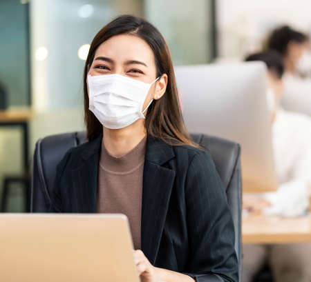 Portrait of asian office employee businesswoman wear protective face mask work in new normal office with interracial colleague in background as social distance practice prevent coronavirus COVID-19.