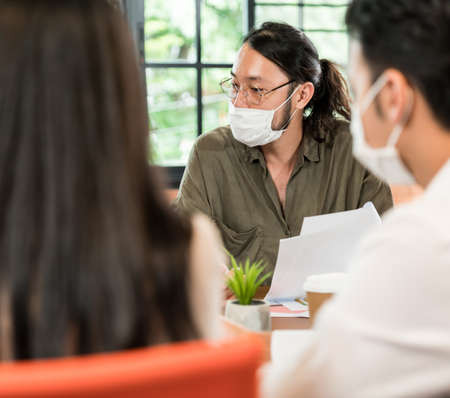 Group of asian business person team meeting and brainstorm in meeting room after office reopen, they wear protective face mask as new normal practice to prevent coronavirus infection. Banque d'images