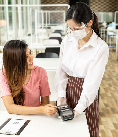 Asian woman customer make contactless credit card payment after eating out in new normal social distance restaurant to reduce touching. Online contactless and technology concept. Banque d'images - 155725381