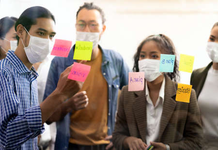 Interracial asian business team brainstorming idea at office meeting room after reopen due to coronavirus COVID-19 city lockdown. They wear face mask reduce risk to infection as new normal lifestyle. Banque d'images