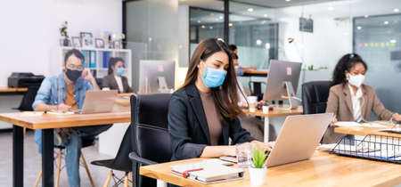 Panoramic group of business worker team wear protective face mask in new normal office with social distance practice with hand sanitiser alcohol gel on table prevent coronavirus COVID-19 spreading Banque d'images