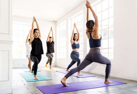 Group of young sporty attractive asian people practicing yoga lesson on Warrior and crescent pose with instructor coach in front in gym studio. Working out, fitness sport and healthy life concept.
