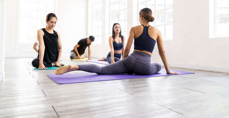 Panoramic of asian yoga instructor coach wearing sportswear bra pants do king pigeon pose in yoga studio with her students in background. Work out fitness healthy lifestyle concept.