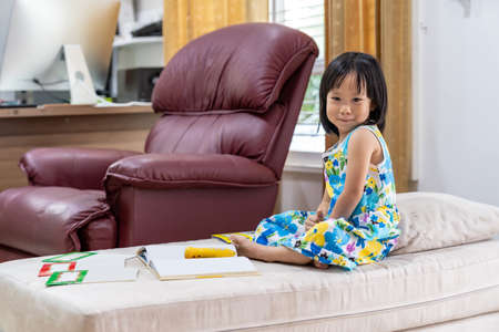 Portrait of Happy asian girl child reading interactive book in living room at home as home schooling while city lockdown because of covid-19 pandemic across the world. Home Schooling concept. Banque d'images