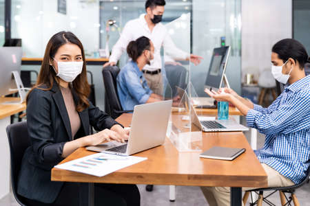 Portrait of asian office employee businesswoman wear protective face mask work in new normal office with interracial team in background as social distance practice prevent coronavirus COVID-19.