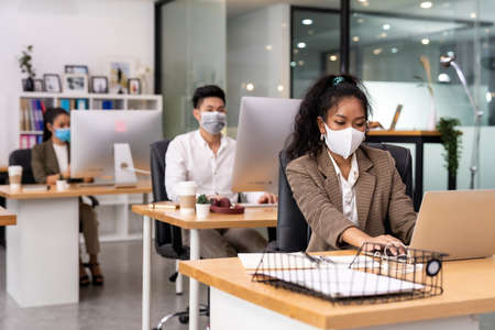 Mixed race of African black and asian business woman wear face mask working in new normal office with social distance to Group of business team people to prevent coronavirus COVID-19 spreading Banque d'images - 155725519