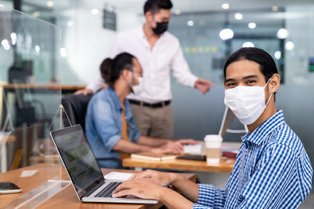 Asian Office employee with protective face mask working in new normal office with social distance practice to his colleague in background prevent coronavirus COVID-19 spreading.