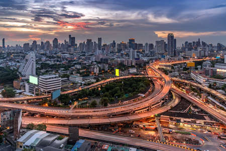 Aerial High angel view of Bangkok downtown highway toll expressway with skyscraper building skylines at sunset dusk. Transportation infrastructure concept.