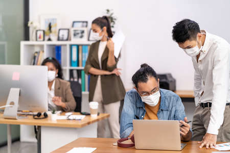 Group of interracial business worker team wear protective face mask in new normal office with social distance practice with hand sanitiser alcohol gel on table prevent coronavirus COVID-19 spreading Banque d'images
