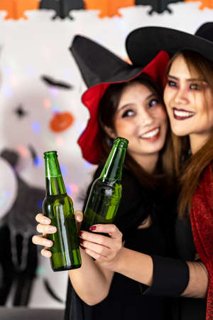 Close up portrait Asian young adult woman wear halloween costume celebrate a Halloween party carnival Festival and cheers with alcohol beer. Halloween celebrate and international holiday concept. Banque d'images