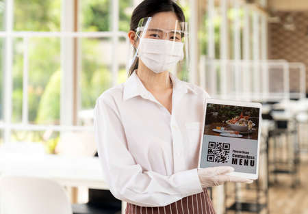 Asian waitress with face mask and face shield hold digital tablet with QR code for customer to scan for online contactless menu. Online contactless and technology concept for new normal restaurant.