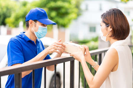 Asian deliver man in blue shirt handling package and give to young woman costumer at house. They wear face mask to reduce coronavirus COVID-19 spreading. Package shopping delivery concept.