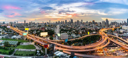 Aerial High angel view of Bangkok downtown highway toll expressway with skyscraper building skylines at sunset dusk. Transportation infrastructure concept. Panoramic web banner crop.