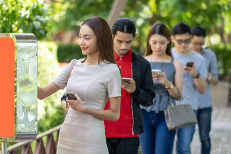 Asian woman using kiosk of food ordering with social distance queue in line befor getting in fast food restaurant. Online technology self service new normal restaurant concept. Stock Photo