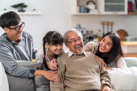 Group Portrait of Happy multigenerational asian family sit on sofa couch in living room with smile. Muti genration family happiness concept. Reklamní fotografie - 156940620