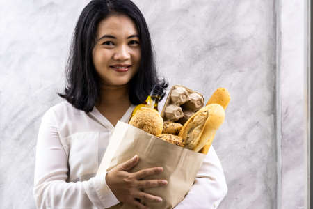 Portrait of asian smile woman housewife holding variety bread in disposable paper bag on grey vintage loft background. Bakery food and drink grocery and domestic life lifestyle concept for delivery. Reklamní fotografie - 156940623