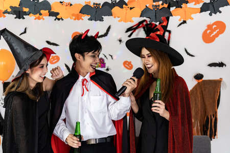 Portrait group of friends asian young adult people celebrate Halloween party carnival festive. They wear Halloween costume sing a song and cheers. Halloween celebrate and international holiday concept Reklamní fotografie - 156940630