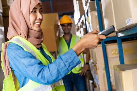 Asian Islam Muslim female warehouse worker do inventory with barcode scanner with Indian worker hold cardboard box in warehouse distribution. For business warehouse inventory and logistic concept. Reklamní fotografie - 156940632