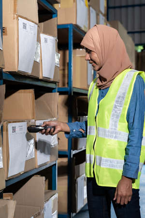 Asian Islam Muslim female warehouse worker do inventory with barcode scanner at product shelf in warehouse distribution. For business warehouse inventory and logistic concept. Reklamní fotografie - 156940641