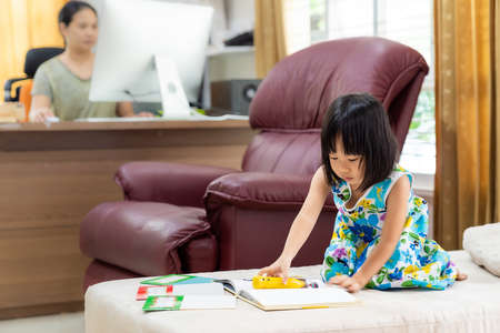 Asian girl child reading interactive book in living room at home as home schooling while her mom working at home because city lockdown because of covid-19 pandemic. Home Schooling concept.