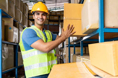 Indian warehouse worker put cardboard box in to shelf with muslim Islam asian worker do inventory in warehouse distribution center environment. Using in business warehouse and logistic concept. Reklamní fotografie - 156940659