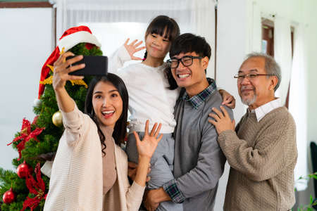 Multigenerational asian Family ,Mom Dad daughter girl and grandfather ,selfie with a Christmas tree after decorate the Christmas ornament prepare season greeting of Merry Christmas and Happy Holidays.
