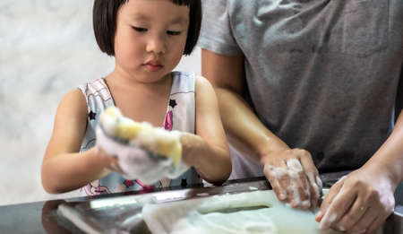 Asian girl washing dish and tableware with her mom, housework for child make executive function for kid. House-working  for kid lifestyle and family concept. Reklamní fotografie - 156940667