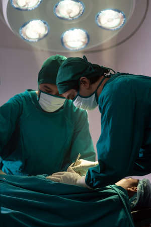 Surgeon doctor and nurse performing Surgical Operation to patient with his team in Operating Room OR. Medical health care Surgery concept. Reklamní fotografie