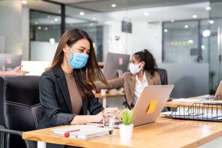 Portrait of asian office employee businesswoman wear protective face mask work in new normal office with interracial team in background as social distance practice prevent coronavirus COVID-19. Reklamní fotografie - 157361306