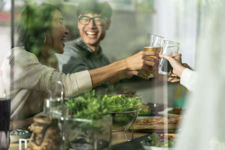 Happy asian multigenerational family of dad mom daughter girl and grandfather cheers together during lunch meal together with joyful. Happy family engagement togetherness concept. Taken outside window Reklamní fotografie