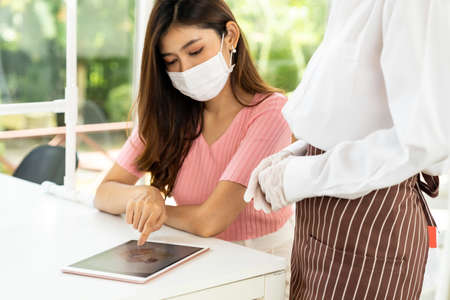 Asian waitress wear facemask and face shield using tablet to show restaurant electronic menu and recommend to customer. New normal technology and lifestyle food and dining concept. Reklamní fotografie