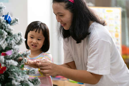 Little asian girl with mom decorating a Christmas tree in her living room with christmas ornament preparing for season greeting together. Multigenerational Family engage and happiness concept.