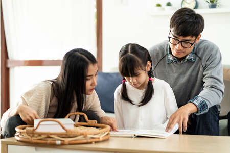 Asian cute girl reading story cartoon book with her mom and dad in living room. Happiness cheerful family and domestic lifestyle concept. Reklamní fotografie - 157361527