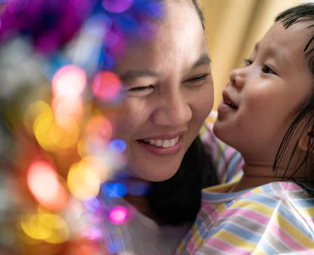 Little asian girl with mom decorating a Christmas tree in her living room with christmas ornament preparing for season greeting together. Multigenerational Family engage and happiness concept. Reklamní fotografie - 157309021