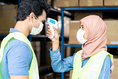 Islam asian warehouse worker taking temperature to worker before getting in factory after reopening from city lockdown from COVID-19 coronavirus pandemic in distribution center environment. Side view.