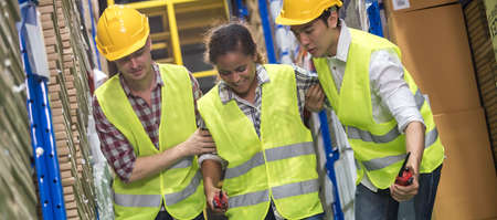 Panoramic Two warehouse workers help their colleague team after accident while working. Using for industrial safety first and business insurance concept.