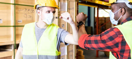 Panoramic Interracial warehouse worker with face mask do elbow bump for alternative greeting after factory reopen from city lockdown cause of coronavirus COVID-19 pandemic.