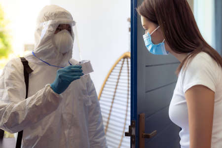 Medical staff in PPE suit show his ID card to patient to identified himself at home before doing swab for COVID-19 at home delivery. Delivery coronavirus covid-19 test at home concept.