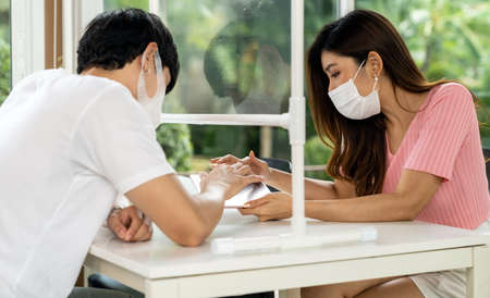 Asian couple customers looking menu from digital tablet. They sat on social distancing table for new normal lifestyle in restaurant after coronavirus covid-19 pandemic