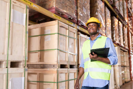 Portrait of african black warehouse worker hold clipboard and looking forward in large warehouse distribution center environment. Using in business warehouse and logistic concept. Reklamní fotografie
