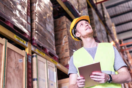 Portrait white caucasian warehouse worker use digital tablet for inventory check in large warehouse distribution center. Reopening traditional business warehouse and logistic concept Reklamní fotografie