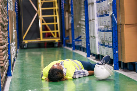 African black warehouse manager lying down. On factory ground after injured from accident while working. Using for industrial safety first and business insurance concept.