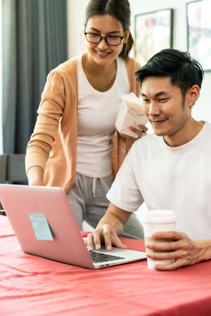 Asian couple work from home in the dining room with delivery take away food box while city lockdown from coronavirus covid-19 pandemic. New Normal lifestyle working from home. Reklamní fotografie