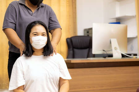 Quarantine asian woman do massage at home with face mask while city lockdown for social distance due to coronavirus pandemic. Massage is one of service business that shutdown while city lockdown. Reklamní fotografie