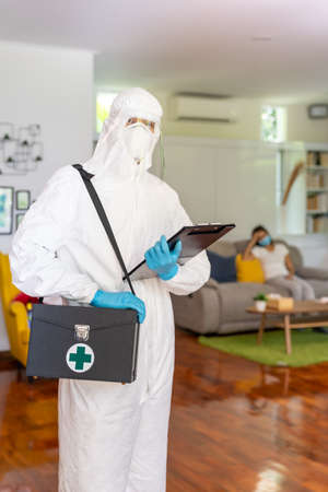Portrait of medical staff in PPE suit with background of asian woman with face mask waiting in living room of apartment .Delivery coronavirus covid-19 test at home concept. Reklamní fotografie
