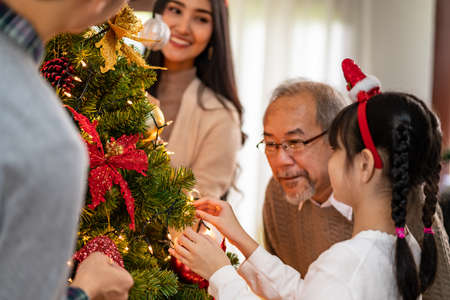 Multigenerational asian Family decorating a Christmas tree. Mom Dad daughter girl and grandfather decorate the Christmas tree prepare for season greeting of Merry Christmas and Happy Holidays. Reklamní fotografie